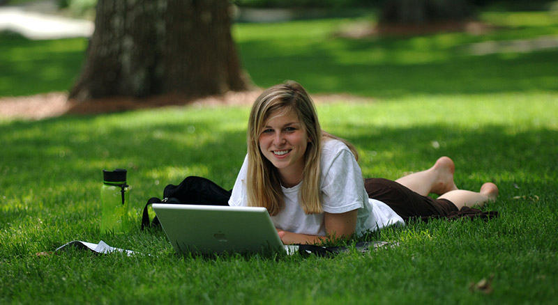 Female student with laptop in the Grove